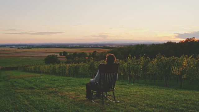 man rocking in rocking chair in lawn overlooking idyllic rural sunset landscape, real time - dondolarsi video stock e b–roll