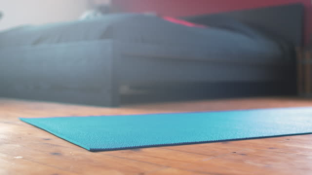 vídeos de stock e filmes b-roll de man rolling out yoga mat at home - rolar