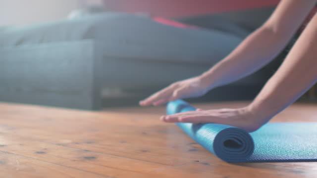 menschen, die yoga-matte zu hause ausrollen - gymnastikmatte stock-videos und b-roll-filmmaterial