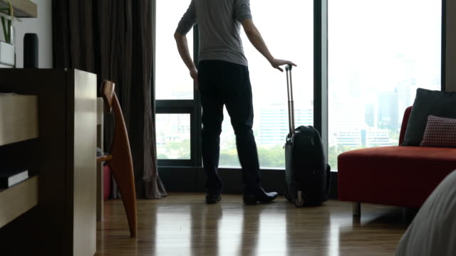 man rolling suitcase wheels into hotel - wheeled luggage stock videos and b-roll footage