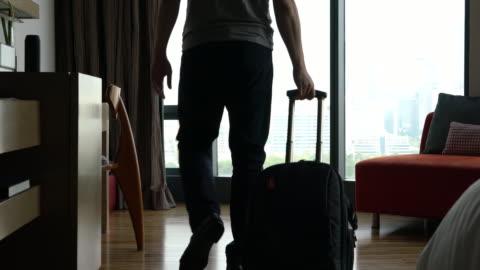 vídeos de stock, filmes e b-roll de homem rolando as rodas da mala em hotel - mala de rodinhas