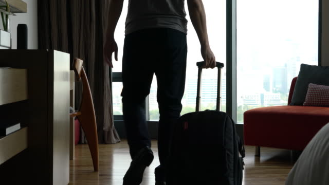 Man rolling Suitcase wheels into hotel