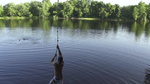 ms ts slo mo man rope swinging into river / farmington, connecticut, united states - 屋外遊具点の映像素材/bロール