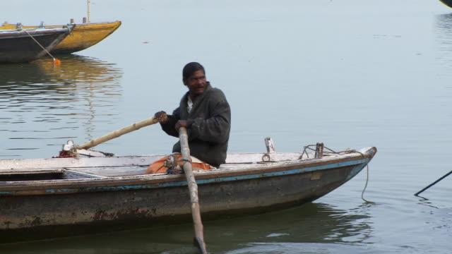 Man rowing a boat away from shore. India.