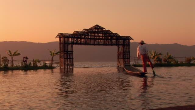 man rowing boat with his leg - auf einem bein stock-videos und b-roll-filmmaterial