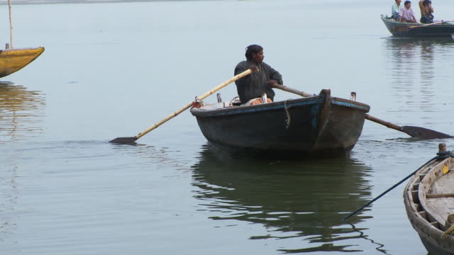 Man rowing his boat away from shore. India.
