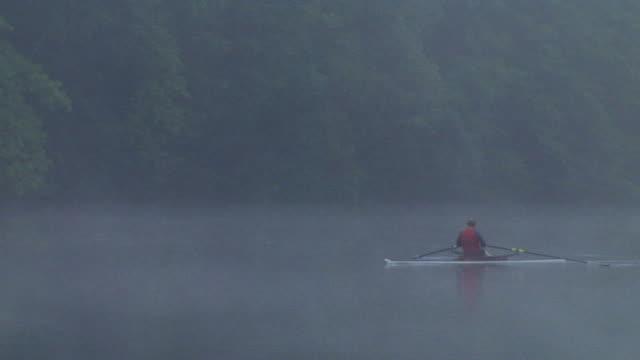 vídeos y material grabado en eventos de stock de ws pan rv man rowing in single scull on the connecticut river in fog at dawn/ hanover, new hampshire, usa - remo con espadilla