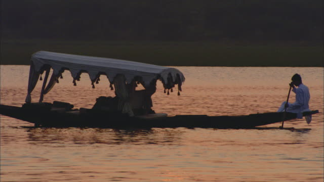WS Man rowing narrow boat in Lake Pichola at sunset / Udaipur, India