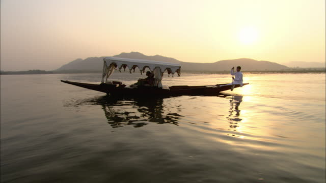 WS POV PAN Man rowing narrow boat with two passengers in Lake Pichola with Lake Palace and mountains in background / Udaipur, India