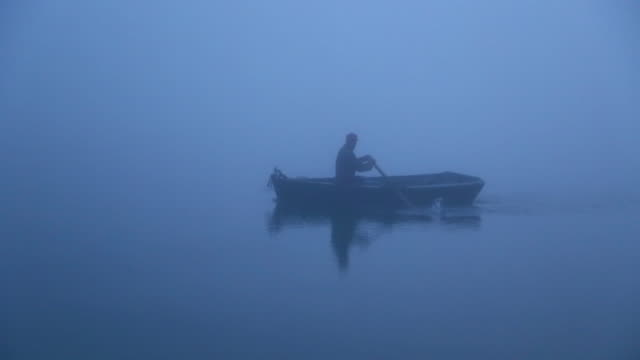 Man rowing Rowboat across water in fog