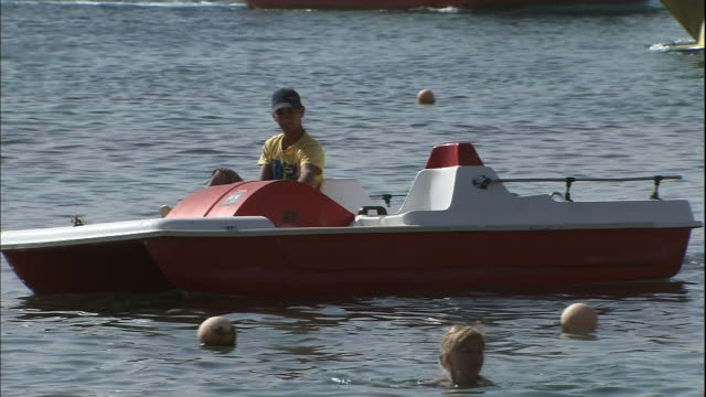 stockvideo's en b-roll-footage met a man rows a pedalo in the red sea. - waterfiets