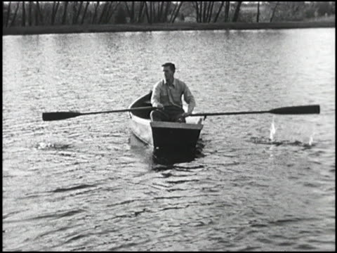 vídeos de stock e filmes b-roll de man rows away from camera in small boat using oars with uneven lengths; keeps reajusting direction of boat man rowing across lake with uneven oars on... - 1949