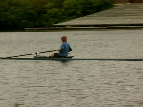 a man rows down the charles river past a boathouse and harvard's eliot house tower - チャールズ川点の映像素材/bロール