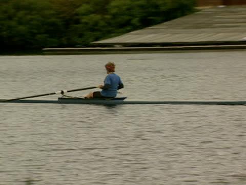 vídeos y material grabado en eventos de stock de a man rows down the charles river past a boathouse and harvard's eliot house tower - río charles