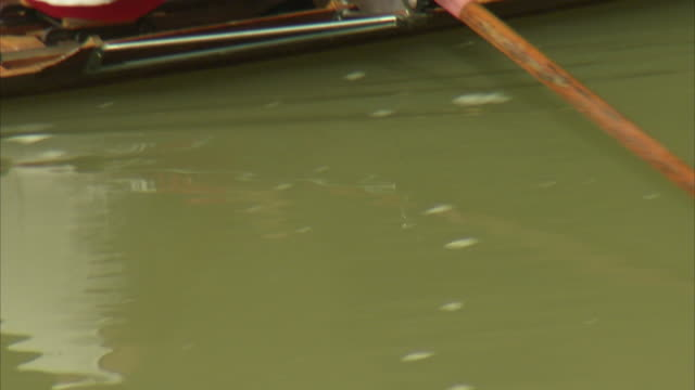 a man rows in a rowing boat on ponte vecchio in florence, italy. - ruderboot stock-videos und b-roll-filmmaterial