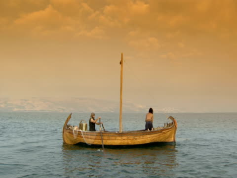 stockvideo's en b-roll-footage met a man rows jesus across the sea of galilee in a fishing boat. - mid volwassen mannen