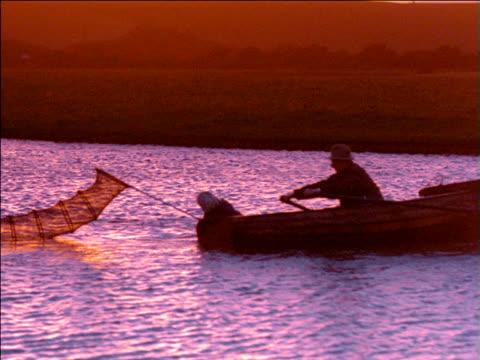 vídeos de stock e filmes b-roll de man rows small boat across river as boy pulls net through water, uk - embarcação de lazer
