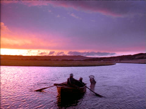 vídeos de stock e filmes b-roll de man rows small boat across river at sunset as boy attempts to catch fish, uk - embarcação de lazer
