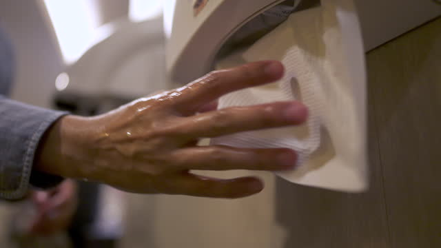 man rubbing wet hands with tissue paper in public toilet. - tissue paper stock videos & royalty-free footage