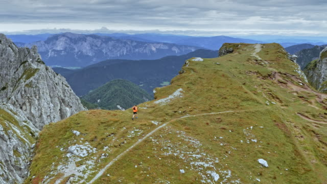 AERIAL Man running across a high mountain ridge overlooking the surrounding mountains