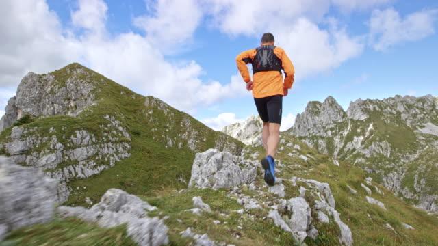 vídeos de stock, filmes e b-roll de slo mo homem atravessando uma cordilheira alta nas montanhas - colina acima