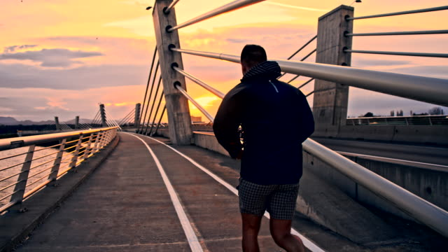 TS Man Running Across The Bridge At Sunrise