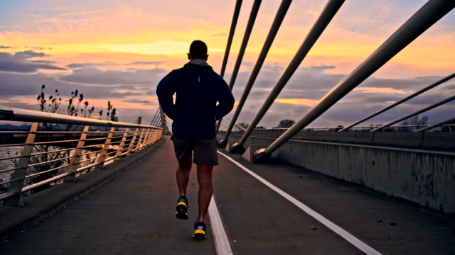 stockvideo's en b-roll-footage met ts man running across the bridge - schemering