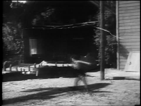 vídeos y material grabado en eventos de stock de man running across yard from collapsed house / feature - 1928
