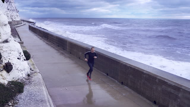 man running alone by a stormy sea - mid adult men stock videos & royalty-free footage
