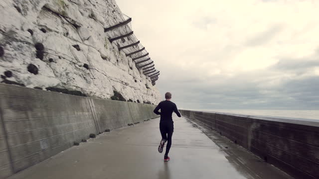 man running alone next to the sea wall and the cliffs - rock face stock videos & royalty-free footage