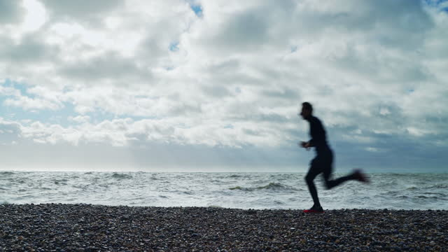 man running along beach next to stormy sea running along the beach - atmosphere filter stock videos & royalty-free footage