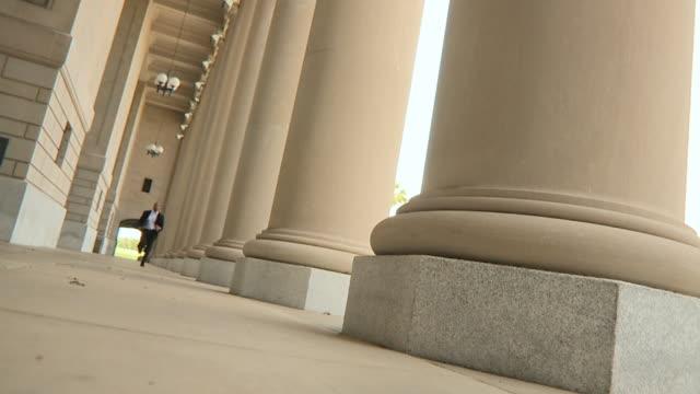 SLO MO WS LA CANTED Man running along colonnade towards camera, Jacksonville, Florida, USA