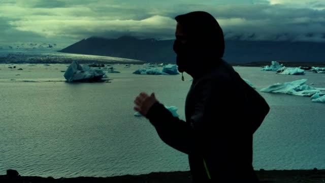 vídeos de stock, filmes e b-roll de homem correndo ao longo da lagoa glaciar - boa postura