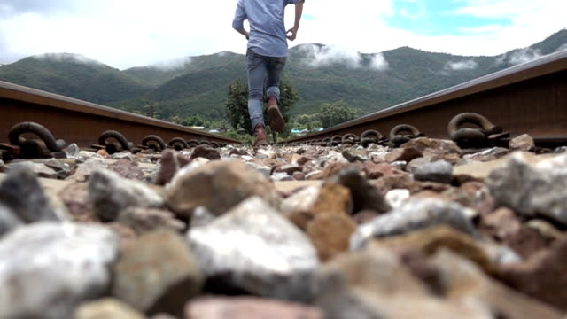 man running along the railroad slow motion. - tramway stock videos and b-roll footage