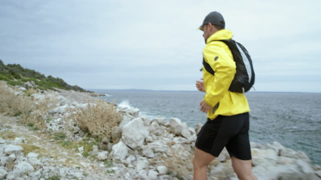 Man running along the rugged beach in bad weather