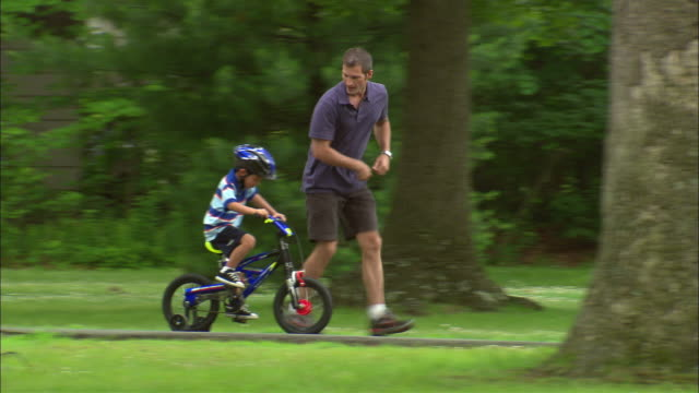 ws pan man running alongside boy as boy learns to ride a bicycle in a park/ fanwood, new jersey - life events stock videos & royalty-free footage