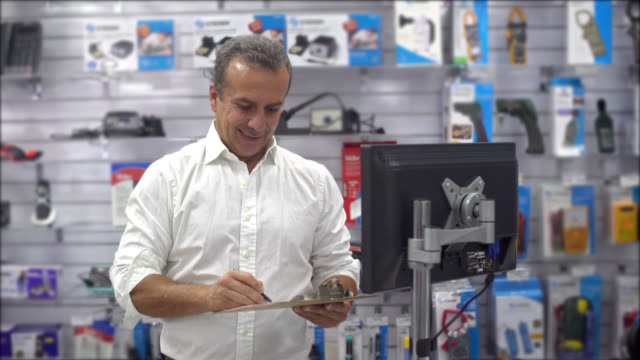 man running an electronics store - checklist stock videos & royalty-free footage