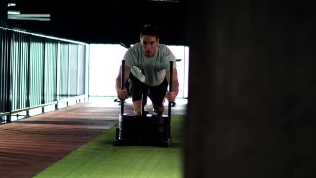 man running and pushing heavy sled in the gym - pushing stock videos & royalty-free footage