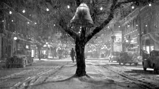 vídeos de stock, filmes e b-roll de a man running down a snowy main street decorated for christmas. - 1946