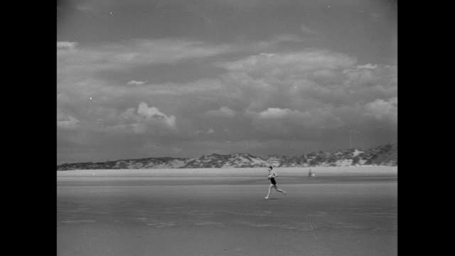 vídeos de stock e filmes b-roll de montage man running down the beach and diving into the ocean / united kingdom - só um rapaz