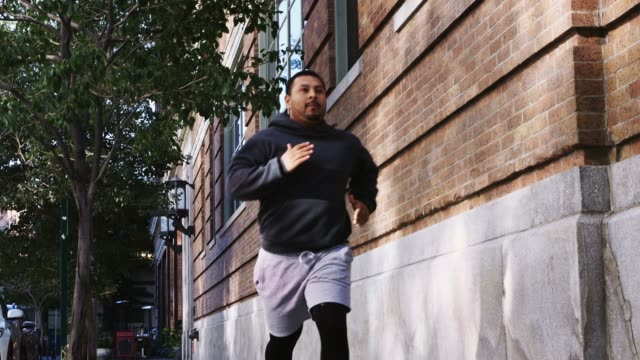 man running down treelined city street - running shorts stock videos & royalty-free footage