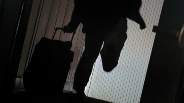 canted silhouette man running frantically through jetway with wheeled baggage + arm raised - human limb stock videos & royalty-free footage