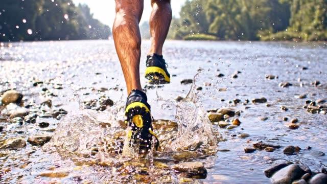 vídeos de stock, filmes e b-roll de slo mo homem correndo em um rio raso - corrida cross country