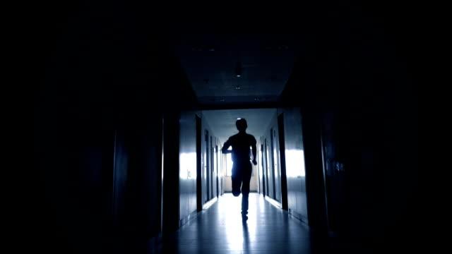 vídeos de stock e filmes b-roll de man running in black corridor - corredor caraterística de construção