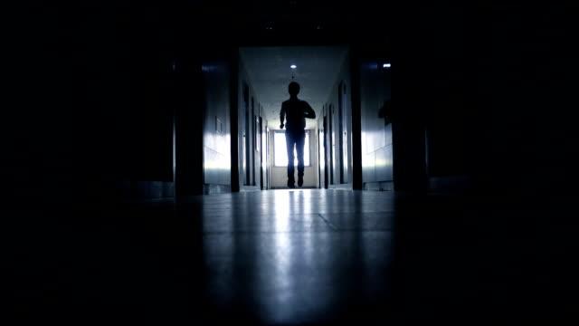 vídeos de stock, filmes e b-roll de homem correndo no corredor preto - escuro