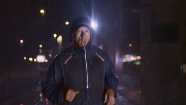 SLO MO Man running in city at night in heavy rain