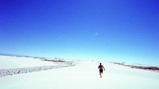 vídeos de stock e filmes b-roll de overexposed selective focus man running in desert toward + past camera / white sands, new mexico - super exposto