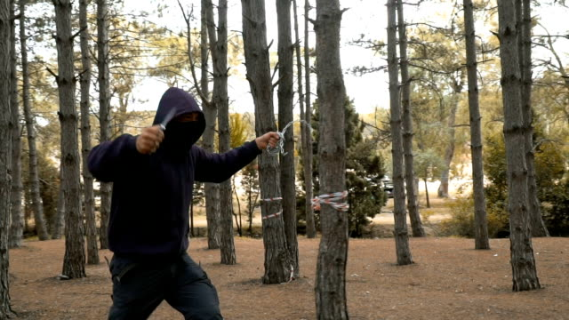 man running in forest and holding knife and chain - knife crime stock videos & royalty-free footage