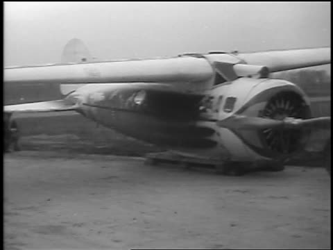 b/w 1935 man running in front of winnie mae prop plane on airfield / cleveland oh / newsreel - 1935 stock videos & royalty-free footage