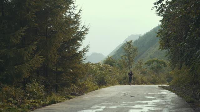 vidéos et rushes de man running in mountain road - seulement des jeunes hommes